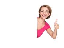 Kvinnan med banret som visar tummarna, up tecknet Royaltyfri Foto