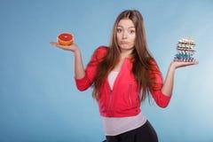 Kvinnan med bantar preventivpillerar och grapefrukten för viktförlust Royaltyfria Bilder