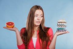 Kvinnan med bantar preventivpillerar och grapefrukten för viktförlust Arkivbild
