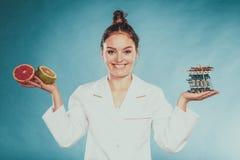 Kvinnan med bantar preventivpillerar och grapefrukter för viktförlust Royaltyfri Foto