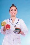 Kvinnan med bantar preventivpillerar och grapefrukter för viktförlust Arkivfoton