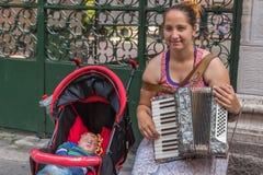 Kvinnan med barnet som gör pengar Arkivfoton