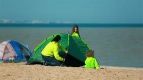 Kvinnan med barnet upprättar tältet på kusten av fjärden för en familjferie stock video