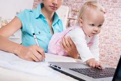 Kvinnan med behandla som ett barn i köket som arbetar med bärbara datorn Royaltyfri Bild