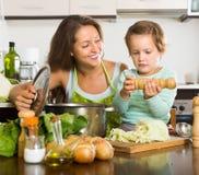 Kvinnan med behandla som ett barn matlagning på kök Royaltyfri Bild