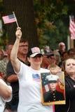Kvinnan med bilden av mannen älskade en vinkar USA-flaggan på räddningen som vårt kors samlar, Knoxville, Iowa Arkivbilder