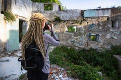 Kvinnan med blonda dreadlocks tar bilder av Abandoned byggnader Royaltyfri Bild