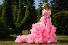 Kvinnan med blonda lås som bär den rosa aftonklänningen med den fluffiga kjolen, poserar i botanisk trädgård på gräset fotografering för bildbyråer