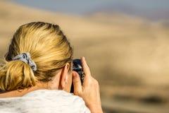 Kvinnan med blont hår står på stranden arkivbild