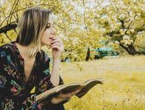 Kvinnan med boken i v?r parkerar royaltyfri fotografi