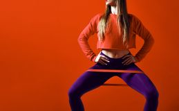 Kvinnan med bra fysik som gör sträckning, utarbetar med elastiska musikband royaltyfri bild