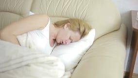 Kvinnan med buk- smärtar att ligga på soffan Flicka som dricker preventivpillersmärtstillande medel