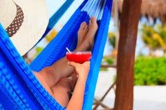 Kvinnan med coctailen kopplade av i hängmatta på stranden Arkivbild