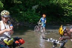 Kvinnan med cykeln korsar floden royaltyfria bilder