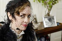 Kvinnan med den chic hatten och skyler Royaltyfri Bild