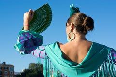 Kvinnan med den gröna den flamencoklänningen och fanen arkivfoto
