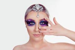 Kvinnan med den konstnärliga purpurfärgade makeupfjädern för blåa ögon på ögonfrans som rymmer silversmycken på head visningmanik royaltyfri fotografi