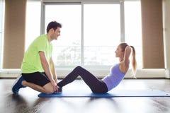 Kvinnan med den personliga instruktören som att göra sitter, ups i idrottshall Royaltyfri Fotografi