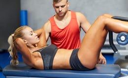 Kvinnan med den personliga instruktören som att göra sitter, ups i idrottshall Arkivfoto