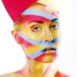 Kvinnan med det idérika geometrisminket som är rött, gulnar, slösar closeupen royaltyfria bilder