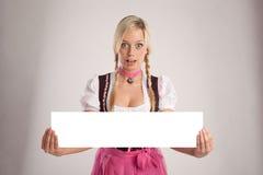 Kvinnan med dirndlen rymmer en tom signboard royaltyfri bild