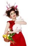 Kvinnan med en kanin, ägg och blommor fjädrar det easter begreppet Arkivfoto
