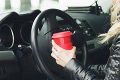 Kvinnan med en röd kopp av den varma drinken håller hjulet av en bil Arkivfoto