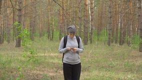 Kvinnan med en ryggsäck går till och med den främre sikten för skogen stock video