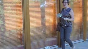 Kvinnan med en selfiepinne går vidare dörren stock video