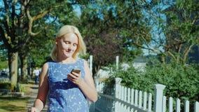 Kvinnan med en smartphone i hennes hand promenerar gatan av en liten stad i Förenta staterna Med hennes lopp stock video
