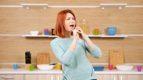 Kvinnan med en träsked i händer sjunger på köket