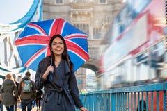 Kvinnan med ett brittiskt flaggaparaply går på tornbron arkivfoto