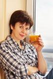 Kvinnan med ett exponeringsglas av fruktsaft sitter nära fönstret Royaltyfri Fotografi