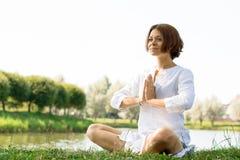 Kvinnan med ett fridfullt blicksammanträde på gräset i lätt poserar Royaltyfri Bild