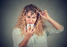 Kvinnan med exponeringsglas som har problem som ser telefonen, har visionproblem Fotografering för Bildbyråer
