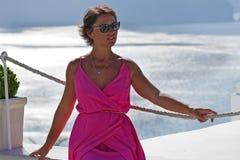 Kvinnan med fuchsiaklänningen beundrar det Oia landskapet i Santorini royaltyfri foto
