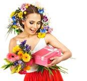 Kvinnan med gåvan boxas och blommar. Arkivfoton