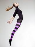 Kvinnan med görar perfekt förkroppsligar hoppa iklädd purpurfärgad randig strumpbyxor och svärtar bästa arkivbild