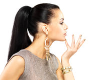 Kvinnan med guld- spikar och härliga guld- smycken Royaltyfri Bild