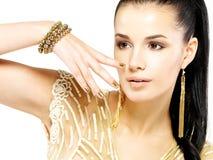 Kvinnan med guld- spikar och härliga guld- smycken Arkivfoton