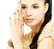 Kvinnan med guld- spikar och härliga guld- smycken Royaltyfria Bilder