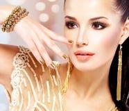 Kvinnan med guld- spikar och härliga guld- smycken Royaltyfri Fotografi