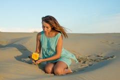 Kvinnan med gulnar rosa sitter på sanden Arkivbild