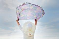 Kvinnan med händer up att rymma en halsduk Royaltyfri Fotografi