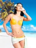Kvinnan med härligt förkroppsligar i bikini på stranden Royaltyfri Fotografi