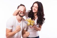 Kvinnan med hållande pojkvänner för det stora toothy leendet synar ge honom en gåva för valentins dag Royaltyfria Foton
