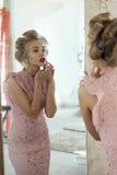 Kvinnan med hårrullar i spegeln korrigerar smink arkivbild