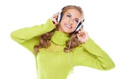 Kvinnan med hörlurar lyssnar till musik royaltyfria foton