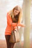 Kvinnan med handväskan som är utomhus- i höst, parkerar Royaltyfria Bilder