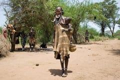 Kvinnan med henne behandla som ett barn av den Mursi stammen Arkivfoton